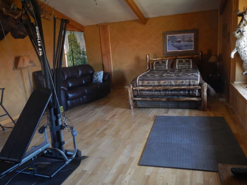Moose Den bedroom with Bowflex machine, yoga mat, and ab incline bench, direct access to backyard, private entrance and private bathroom