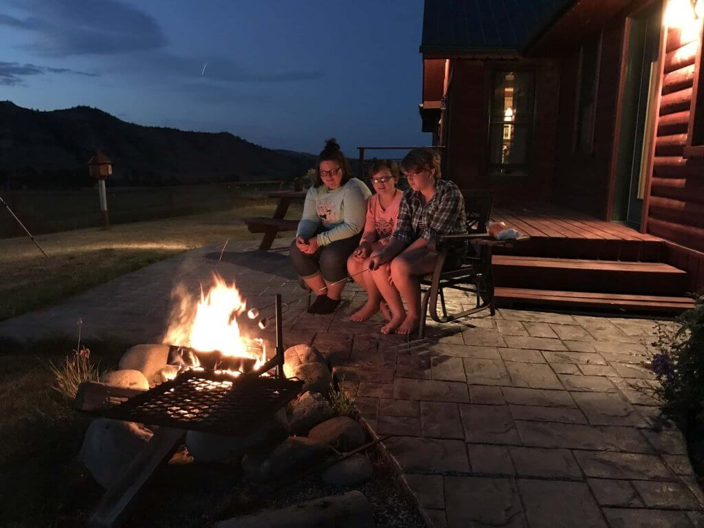 girls roasting marshmallows on a beautiful Wyoming night in the backyard next to the fire pit